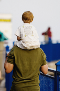 young child riding on mans shoulders