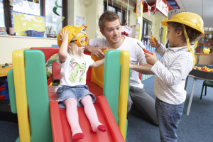 man playing with children in playroom