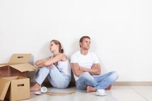 upset couple sitting on floor with backs turned to eachoter