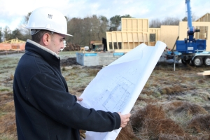 man reading blueprints at construction site