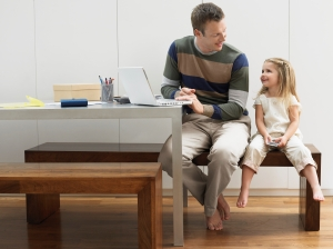 man working at desk talking to young girl