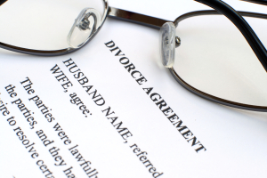 glasses sitting on top of divorce agreement document